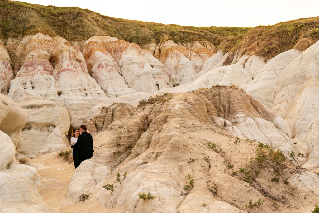 A newly engaged couple hanging out in each others arms among the rock formations of the Calhan Paint Mines. Photo by Gabby Jockers Photography. Paint mines engagement photography, Paint mines engagement photos, Paint mines engagement session, colorado springs engagement photos, colorado springs engagement session, colorado engagement photos, colorado engagement session, hiking engagement, adventure photos, adventure session, couples photos, paint mines colorado, paint mines calhan, paint mines elopement, colorado elopement