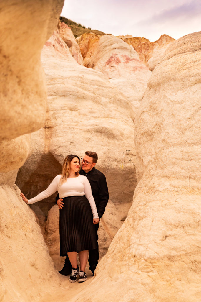 A man with his arms around his fiance while they stand among white rock walls in the Calhan Paint Mines. Photo by Gabby Jockers Photography. Paint mines engagement photography, Paint mines engagement photos, Paint mines engagement session, colorado springs engagement photos, colorado springs engagement session, colorado engagement photos, colorado engagement session, hiking engagement, adventure photos, adventure session, couples photos, paint mines colorado, paint mines calhan, paint mines elopement, colorado elopement