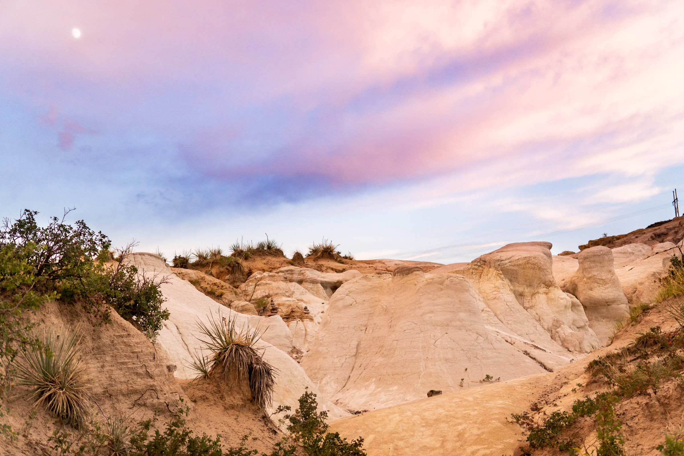 The Calhan Paint Mines with a cloudy twilight sky and full moon. Photo by Gabby Jockers Photography. Paint mines engagement photography, Paint mines engagement photos, Paint mines engagement session, colorado springs engagement photos, colorado springs engagement session, colorado engagement photos, colorado engagement session, hiking engagement, adventure photos, adventure session, couples photos, paint mines colorado, paint mines calhan, paint mines elopement, colorado elopement