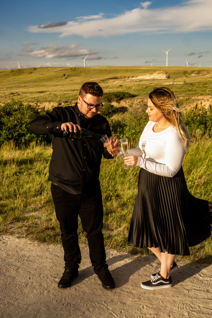 A newly engaged couple toasting with champagne in front of a plain covered in wind turbines. Photo by Gabby Jockers Photography. Paint mines engagement photography, Paint mines engagement photos, Paint mines engagement session, colorado springs engagement photos, colorado springs engagement session, colorado engagement photos, colorado engagement session, hiking engagement, adventure photos, adventure session, couples photos, paint mines colorado, paint mines calhan, paint mines elopement, colorado elopement