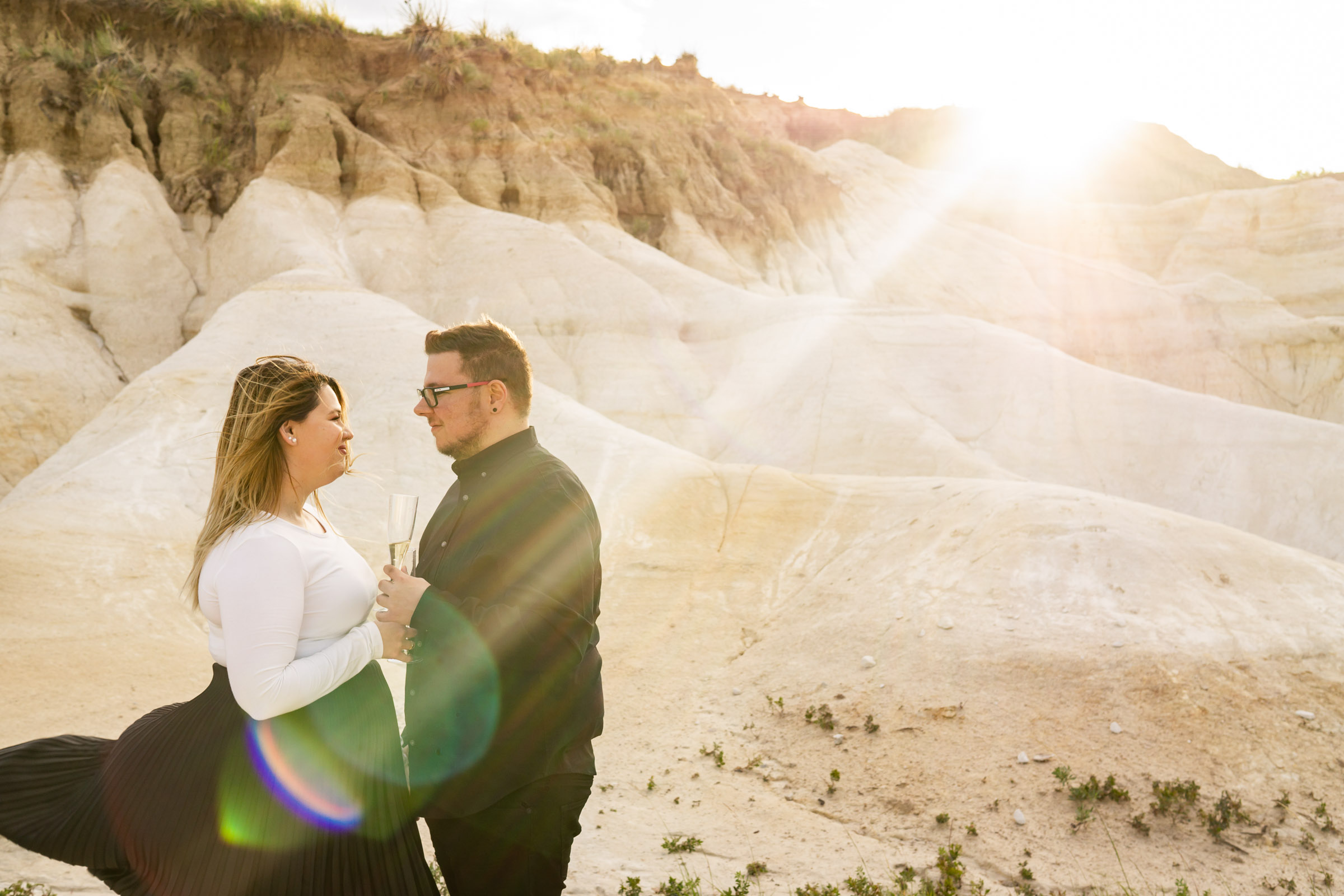 A man and woman wearing black and while toasting with champagne in front of the bright shining sun at the Calhan Paint Mines. Photo by Gabby Jockers Photography. Paint mines engagement photography, Paint mines engagement photos, Paint mines engagement session, colorado springs engagement photos, colorado springs engagement session, colorado engagement photos, colorado engagement session, hiking engagement, adventure photos, adventure session, couples photos, paint mines colorado, paint mines calhan, paint mines elopement, colorado elopement