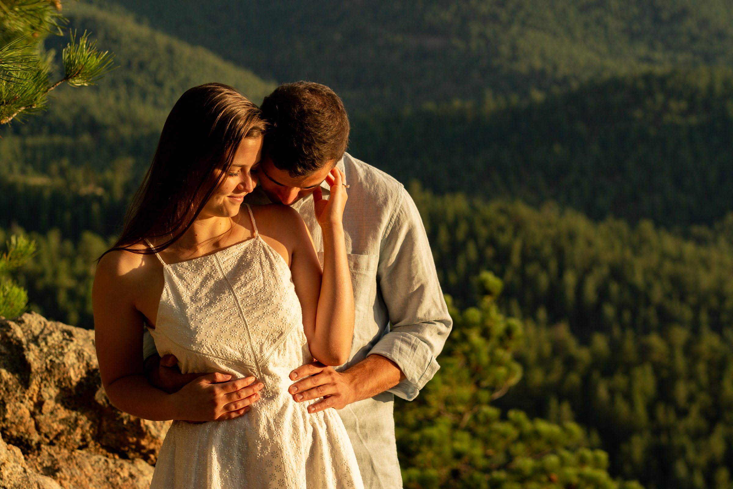 An engaged couple soaking in each others presence in the harsh afternoon light outside on a mountain. Photo by Gabby Jockers Photography. Colorado engagement photography, Colorado engagement photos, Colorado engagement session, mountain engagement photos,mountain engagement session, mountain photography, hiking engagement session, summer engagement photos, wilderness, hiking, hiking engagement, adventure photos, adventure session, couples photos, evergreen co elopement, colorado elopement, sunset engagement photos