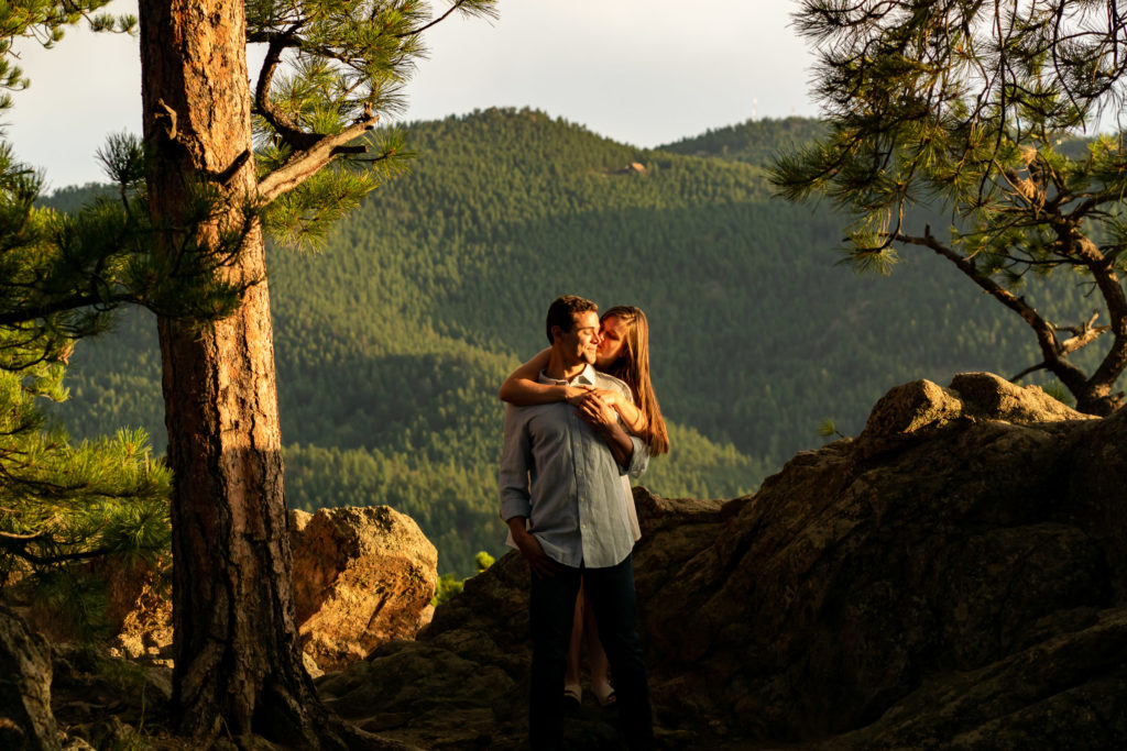 A woman is hugging her partner from behind and laughing while the bright sun shines on them. Photo by Gabby Jockers Photography. Colorado engagement photography, Colorado engagement photos, Colorado engagement session, mountain engagement photos,mountain engagement session, mountain photography, hiking engagement session, summer engagement photos, wilderness, hiking, hiking engagement, adventure photos, adventure session, couples photos, evergreen co elopement, colorado elopement, sunset engagement photos