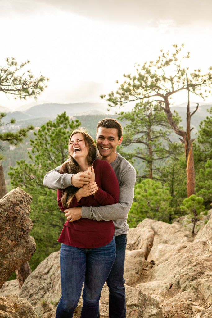 A man is hugging his fiance from behind and makes her laugh while they stand in front of a beautiful mountain vista. Photo by Gabby Jockers Photography. Colorado engagement photography, Colorado engagement photos, Colorado engagement session, mountain engagement photos,mountain engagement session, mountain photography, hiking engagement session, summer engagement photos, wilderness, hiking, hiking engagement, adventure photos, adventure session, couples photos, evergreen co elopement, colorado elopement, sunset engagement photos