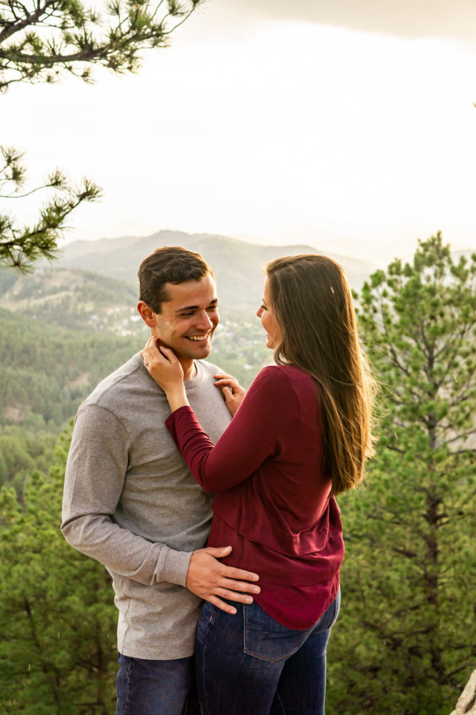 A newly engaged couple laughs together in each others arms after a hike up to a spot with a beautiful mountain view. Photo by Gabby Jockers Photography. Colorado engagement photography, Colorado engagement photos, Colorado engagement session, mountain engagement photos,mountain engagement session, mountain photography, hiking engagement session, summer engagement photos, wilderness, hiking, hiking engagement, adventure photos, adventure session, couples photos, evergreen co elopement, colorado elopement, sunset engagement photos