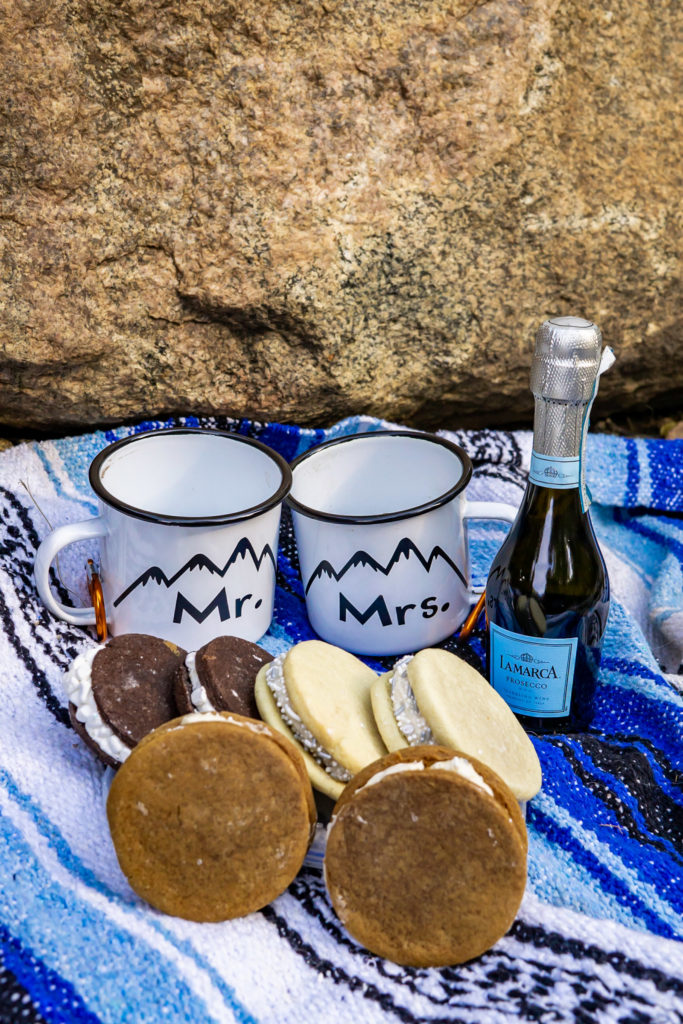 A unique wedding dessert - cookie sammies and mini champagne bottles, arranged as a portable elopement dessert. Photo by Gabby Jockers Photography. Colorado elopement ideas, elopement inspiration, elopement ideas, Colorado elopement photographer, Colorado elopement photography, hiking elopement, backpacking elopement, Rocky Mountain national park wedding, rocky mountains, backpacking wedding, camping wedding, fall wedding, adventure wedding, adventurous elopement, mountain elopement, elopement with dog, dog of honor, best dog