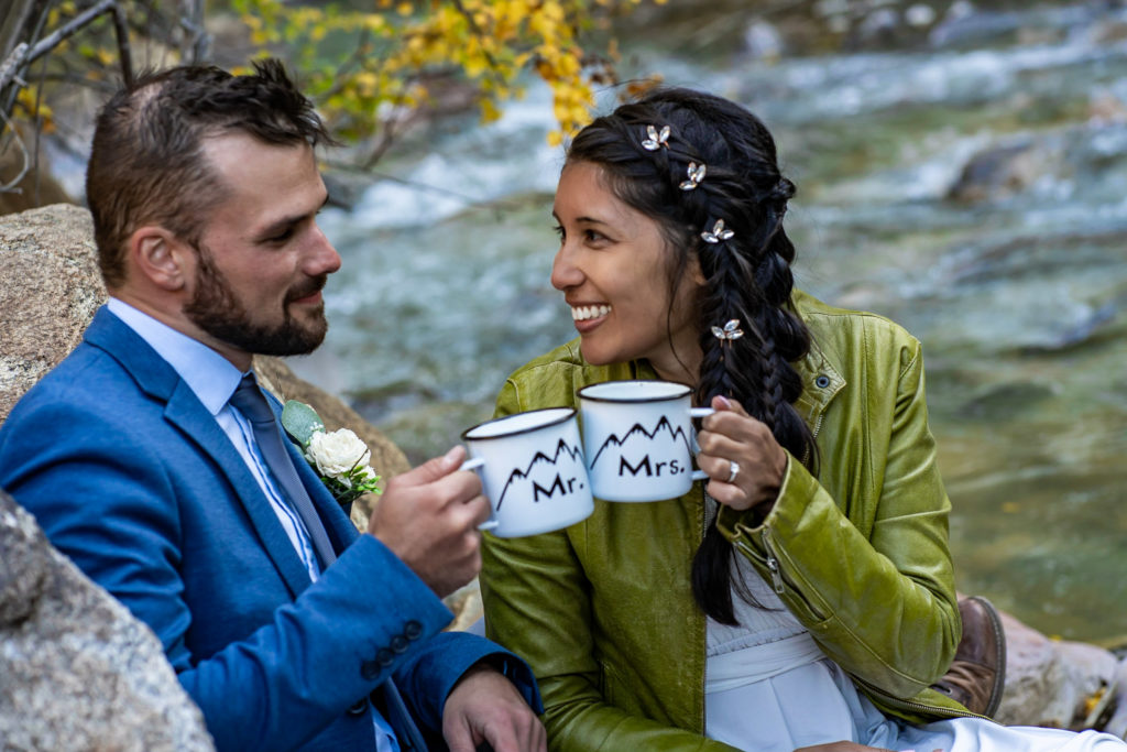 A married couple laugh together while sitting down and holding matching Mr and Mrs tip cups after their elopement ceremony. Photo by Gabby Jockers Photography. Colorado elopement ideas, elopement inspiration, elopement ideas, Colorado elopement photographer, Colorado elopement photography, hiking elopement, backpacking elopement, Rocky Mountain national park wedding, rocky mountains, backpacking wedding, camping wedding, fall wedding, adventure wedding, adventurous elopement, mountain elopement, elopement with dog, dog of honor, best dog