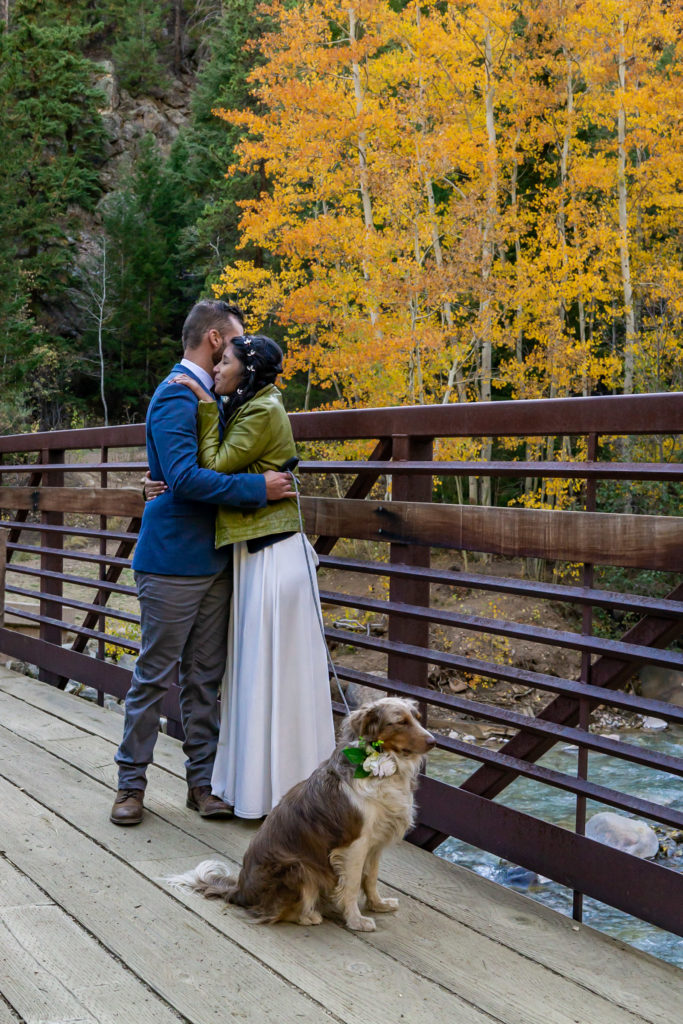 A newly married couple hugging on a bridge with their dog in the fall. Photo by Gabby Jockers Photography. Colorado elopement ideas, elopement inspiration, elopement ideas, Colorado elopement photographer, Colorado elopement photography, hiking elopement, backpacking elopement, Rocky Mountain national park wedding, rocky mountains, backpacking wedding, camping wedding, fall wedding, adventure wedding, adventurous elopement, mountain elopement, elopement with dog, dog of honor, best dog