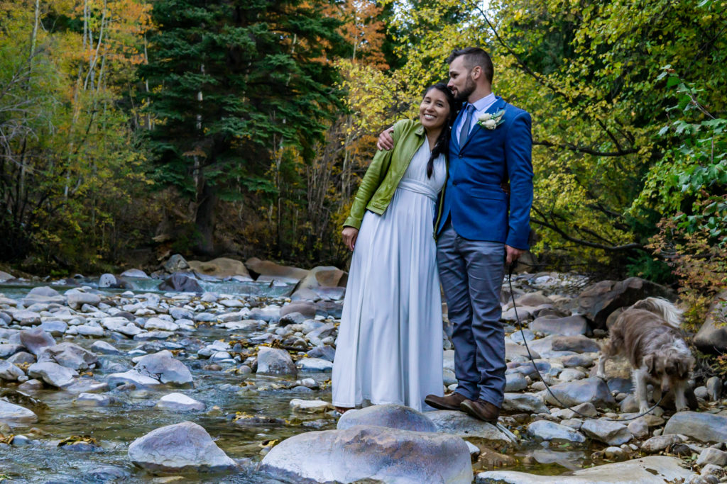 A newly married couple stands side by side over a river in the fall with their dog nearby. Photo by Gabby Jockers Photography. Colorado elopement ideas, elopement inspiration, elopement ideas, Colorado elopement photographer, Colorado elopement photography, hiking elopement, backpacking elopement, Rocky Mountain national park wedding, rocky mountains, backpacking wedding, camping wedding, fall wedding, adventure wedding, adventurous elopement, mountain elopement, elopement with dog, dog of honor, best dog