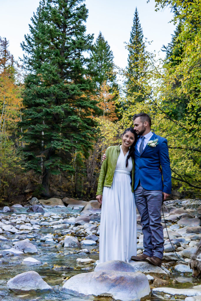 A newly married couple stands side by side over a river in the fall. Photo by Gabby Jockers Photography. Colorado elopement ideas, elopement inspiration, elopement ideas, Colorado elopement photographer, Colorado elopement photography, hiking elopement, backpacking elopement, Rocky Mountain national park wedding, rocky mountains, backpacking wedding, camping wedding, fall wedding, adventure wedding, adventurous elopement, mountain elopement, elopement with dog, dog of honor, best dog