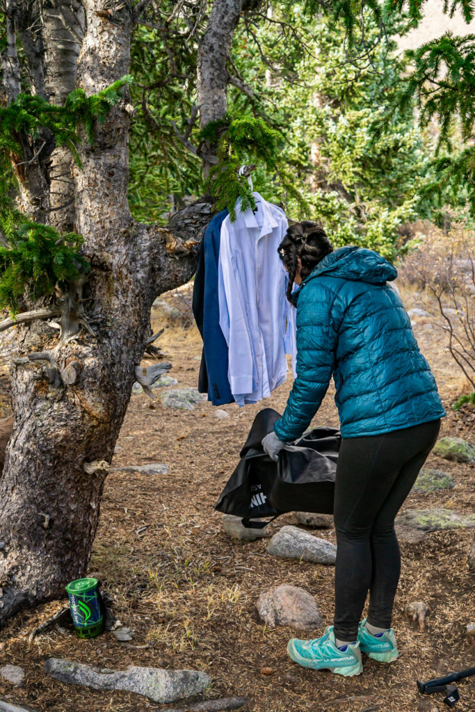 A bride wearing hiking clothes sets up her grooms suit on a tree. Photo by Gabby Jockers Photography. Colorado elopement ideas, elopement inspiration, elopement ideas, Colorado elopement photographer, Colorado elopement photography, hiking elopement, backpacking elopement, Rocky Mountain national park wedding, rocky mountains, backpacking wedding, camping wedding, fall wedding, adventure wedding, adventurous elopement, mountain elopement, elopement with dog, dog of honor, best dog