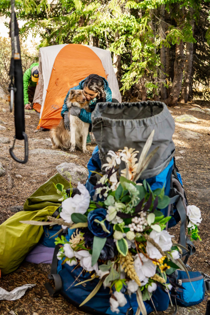 A bride hugging her dog in front of her silk bouquet in a backpack. Photo by Gabby Jockers Photography. Colorado elopement ideas, elopement inspiration, elopement ideas, Colorado elopement photographer, Colorado elopement photography, hiking elopement, backpacking elopement, Rocky Mountain national park wedding, rocky mountains, backpacking wedding, camping wedding, fall wedding, adventure wedding, adventurous elopement, mountain elopement, elopement with dog, dog of honor, best dog