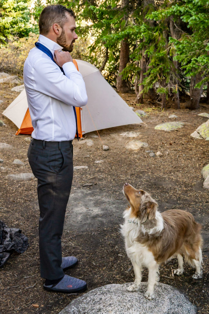 A groom adjusts his tie while his dog of honor looks on. Photo by Gabby Jockers Photography. Colorado elopement ideas, elopement inspiration, elopement ideas, Colorado elopement photographer, Colorado elopement photography, hiking elopement, backpacking elopement, Rocky Mountain national park wedding, rocky mountains, backpacking wedding, camping wedding, fall wedding, adventure wedding, adventurous elopement, mountain elopement, elopement with dog, dog of honor, best dog