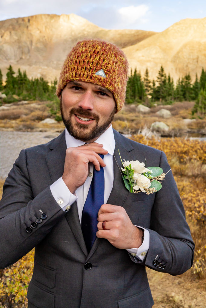 A groom wearing a gray suit, sola wood boutonniere, and knit hat. Photo by Gabby Jockers Photography. Colorado elopement ideas, elopement inspiration, elopement ideas, Colorado elopement photographer, Colorado elopement photography, hiking elopement, backpacking elopement, Rocky Mountain national park wedding, rocky mountains, backpacking wedding, camping wedding, fall wedding, adventure wedding, adventurous elopement, mountain elopement, elopement with dog, dog of honor, best dog