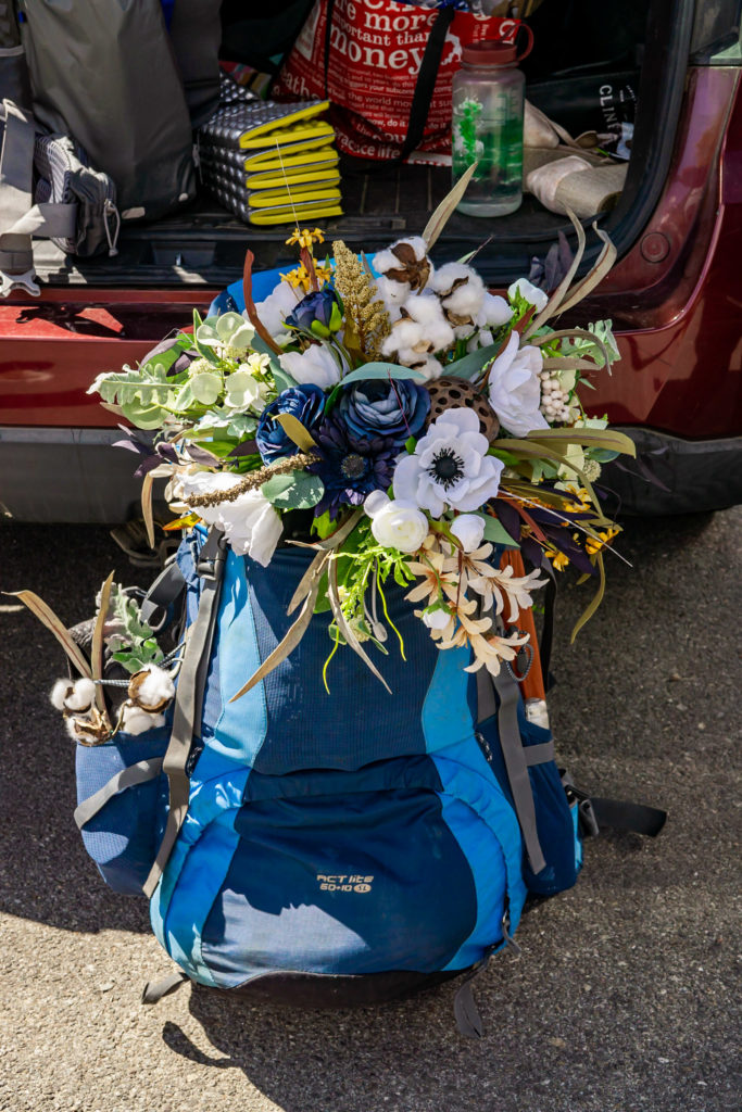 A hiking backpack with a blue silk bouquet sticking out! Photo by Gabby Jockers Photography. Colorado elopement ideas, elopement inspiration, elopement ideas, Colorado elopement photographer, Colorado elopement photography, hiking elopement, backpacking elopement, Rocky Mountain national park wedding, rocky mountains, backpacking wedding, camping wedding, fall wedding, adventure wedding, adventurous elopement, mountain elopement, elopement with dog, dog of honor, best dog