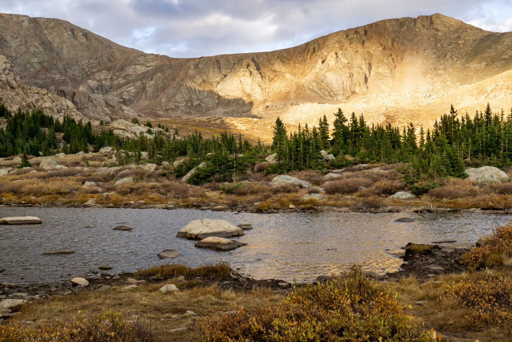 Landscape photo of the mountains behind an alpine lake. Photo by Gabby Jockers Photography. Colorado elopement ideas, elopement inspiration, elopement ideas, Colorado elopement photographer, Colorado elopement photography, hiking elopement, backpacking elopement, Rocky Mountain national park wedding, rocky mountains, backpacking wedding, camping wedding, fall wedding, adventure wedding, adventurous elopement, mountain elopement, elopement with dog, dog of honor, best dog
