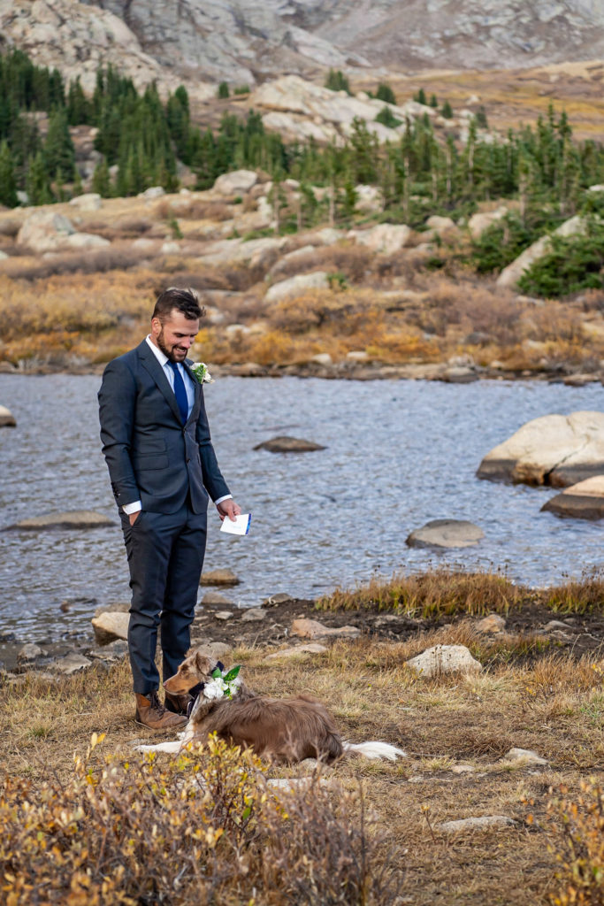 A groom waits for his bridge to arrive at the ceremony. He's wearing a gray suit and has his dog. Photo by Gabby Jockers Photography. Colorado elopement ideas, elopement inspiration, elopement ideas, Colorado elopement photographer, Colorado elopement photography, hiking elopement, backpacking elopement, Rocky Mountain national park wedding, rocky mountains, backpacking wedding, camping wedding, fall wedding, adventure wedding, adventurous elopement, mountain elopement, elopement with dog, dog of honor, best dog