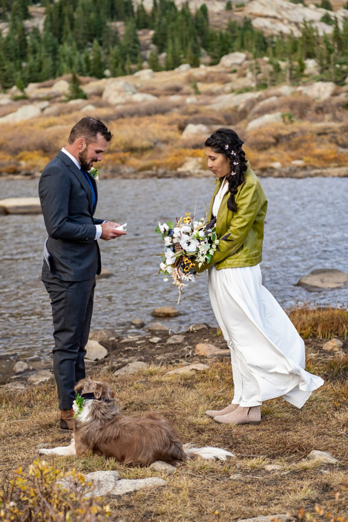Vow ceremony at a lake with a dog. The bride wears a flowy white dress while holding a silk bouquet and green leather jacket and groom wears a gray suit. Photo by Gabby Jockers Photography. Colorado elopement ideas, elopement inspiration, elopement ideas, Colorado elopement photographer, Colorado elopement photography, hiking elopement, backpacking elopement, Rocky Mountain national park wedding, rocky mountains, backpacking wedding, camping wedding, fall wedding, adventure wedding, adventurous elopement, mountain elopement, elopement with dog, dog of honor, best dog
