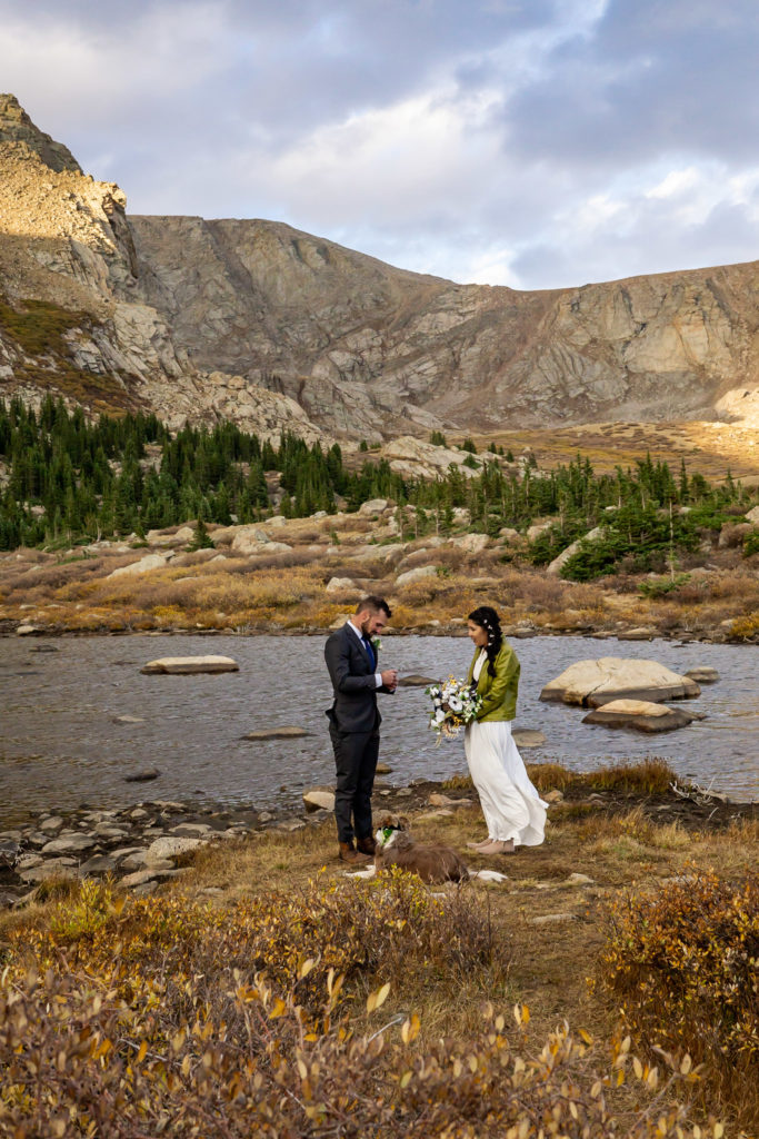 Vow ceremony in front of an alpine lake. The bride wears a flowy white dress while holding a silk bouquet and green leather jacket and groom wears a gray suit. Photo by Gabby Jockers Photography. Colorado elopement ideas, elopement inspiration, elopement ideas, Colorado elopement photographer, Colorado elopement photography, hiking elopement, backpacking elopement, Rocky Mountain national park wedding, rocky mountains, backpacking wedding, camping wedding, fall wedding, adventure wedding, adventurous elopement, mountain elopement, elopement with dog, dog of honor, best dog