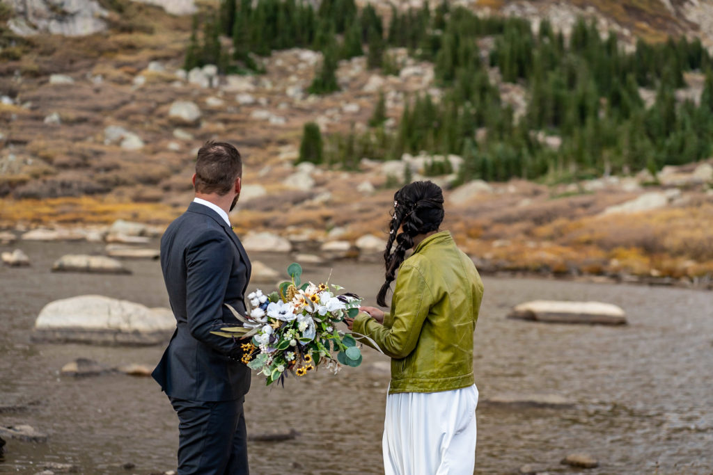 Bride and groom looking away toward an alpine lake. She's holding a silk bouquet with a braid hairstyle. Photo by Gabby Jockers Photography. Colorado elopement ideas, elopement inspiration, elopement ideas, Colorado elopement photographer, Colorado elopement photography, hiking elopement, backpacking elopement, Rocky Mountain national park wedding, rocky mountains, backpacking wedding, camping wedding, fall wedding, adventure wedding, adventurous elopement, mountain elopement, elopement with dog, dog of honor, best dog