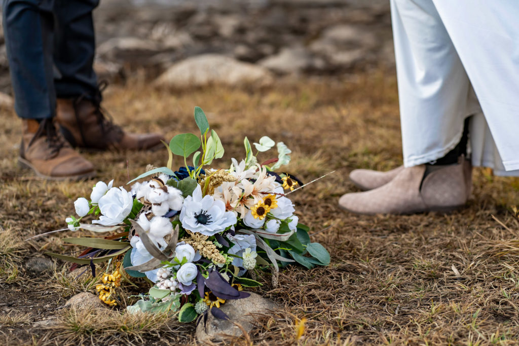 Silk bouquet with white, blue, and green flowers, suede bridal boots, leather groom boots. Photo by Gabby Jockers Photography. Colorado elopement ideas, elopement inspiration, elopement ideas, Colorado elopement photographer, Colorado elopement photography, hiking elopement, backpacking elopement, Rocky Mountain national park wedding, rocky mountains, backpacking wedding, camping wedding, fall wedding, adventure wedding, adventurous elopement, mountain elopement, elopement with dog, dog of honor, best dog