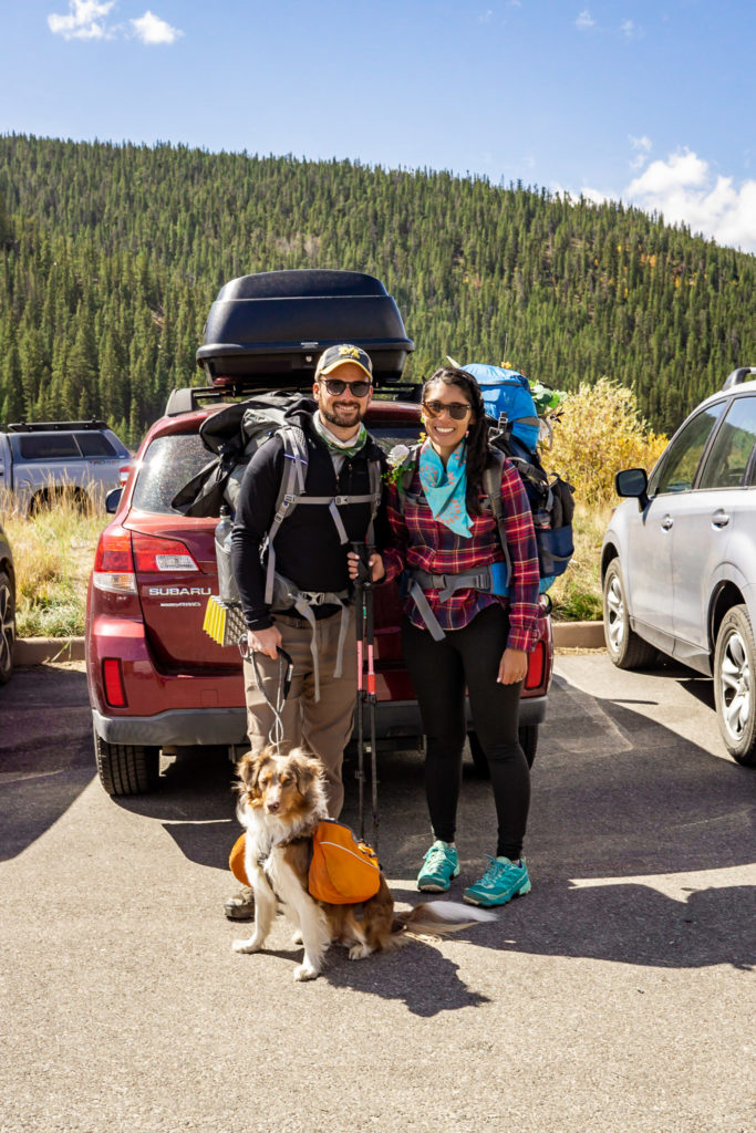A couple standing in front of their car at the trailhead with their dog. Photo by Gabby Jockers Photography. Colorado elopement ideas, elopement inspiration, elopement ideas, Colorado elopement photographer, Colorado elopement photography, hiking elopement, backpacking elopement, Rocky Mountain national park wedding, rocky mountains, backpacking wedding, camping wedding, fall wedding, adventure wedding, adventurous elopement, mountain elopement, elopement with dog, dog of honor, best dog
