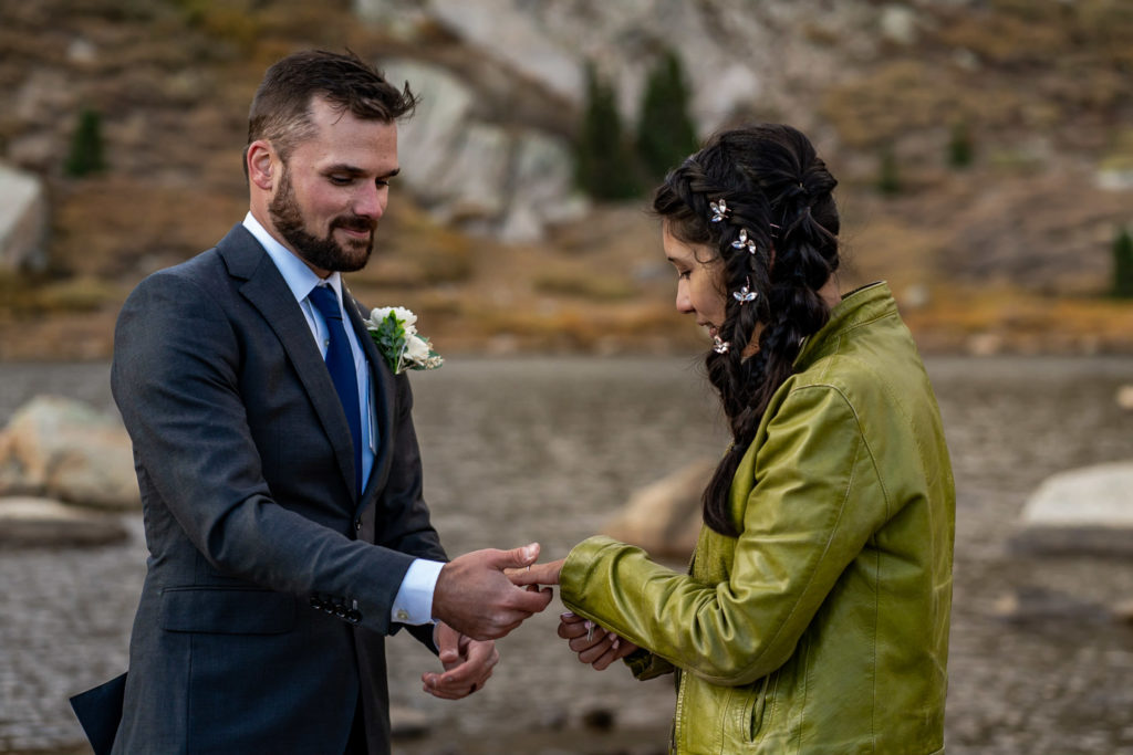 A bride and groom exchanging rings in front of an alpine lake, he's wearing a gray suit and boutonniere and she's wearing a leather jacket with bridal braid hairstyle. Photo by Gabby Jockers Photography. Colorado elopement ideas, elopement inspiration, elopement ideas, Colorado elopement photographer, Colorado elopement photography, hiking elopement, backpacking elopement, Rocky Mountain national park wedding, rocky mountains, backpacking wedding, camping wedding, fall wedding, adventure wedding, adventurous elopement, mountain elopement, elopement with dog, dog of honor, best dog