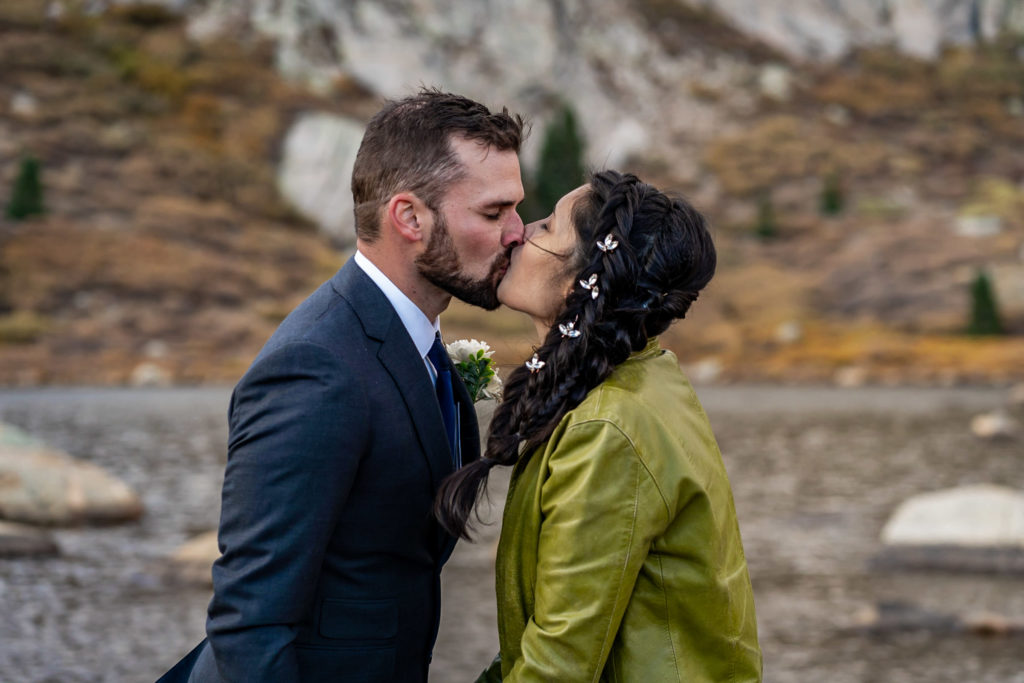 A bride and groom kissing in front of an alpine lake, he's wearing a gray suit and boutonniere and she's wearing a leather jacket with bridal braid hairstyle. Photo by Gabby Jockers Photography. Colorado elopement ideas, elopement inspiration, elopement ideas, Colorado elopement photographer, Colorado elopement photography, hiking elopement, backpacking elopement, Rocky Mountain national park wedding, rocky mountains, backpacking wedding, camping wedding, fall wedding, adventure wedding, adventurous elopement, mountain elopement, elopement with dog, dog of honor, best dog