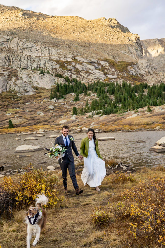 A couple walks hand in hand down the trail with their dog. The bride wears a flowy white dress while holding a silk bouquet and green leather jacket and groom wears a gray suit. Photo by Gabby Jockers Photography. Colorado elopement ideas, elopement inspiration, elopement ideas, Colorado elopement photographer, Colorado elopement photography, hiking elopement, backpacking elopement, Rocky Mountain national park wedding, rocky mountains, backpacking wedding, camping wedding, fall wedding, adventure wedding, adventurous elopement, mountain elopement, elopement with dog, dog of honor, best dog