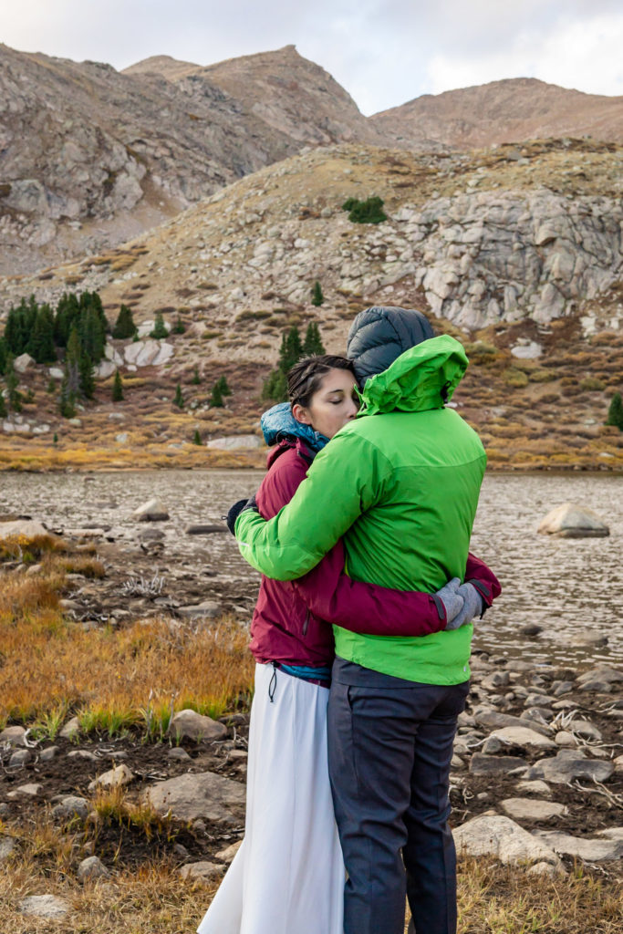 A bride and groom wearing puffy jackets over their wedding clothes, hugging in front of an alpine lake. Photo by Gabby Jockers Photography. Colorado elopement ideas, elopement inspiration, elopement ideas, Colorado elopement photographer, Colorado elopement photography, hiking elopement, backpacking elopement, Rocky Mountain national park wedding, rocky mountains, backpacking wedding, camping wedding, fall wedding, adventure wedding, adventurous elopement, mountain elopement, elopement with dog, dog of honor, best dog