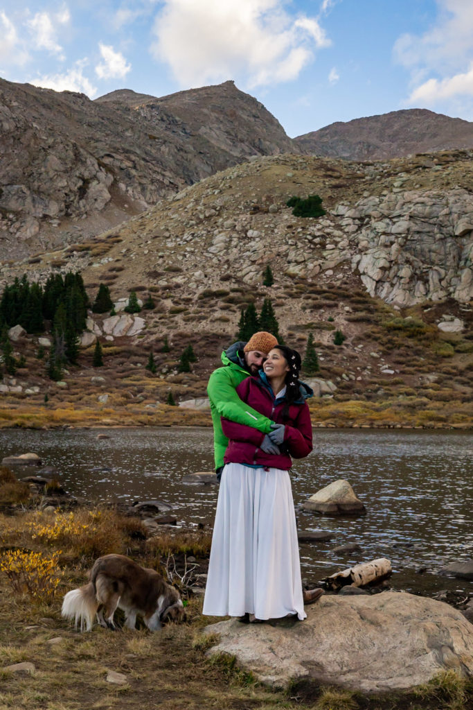 A bride and groom wearing puffy jackets over their wedding clothes, hugging with their dog in front of an alpine lake. Photo by Gabby Jockers Photography. Colorado elopement ideas, elopement inspiration, elopement ideas, Colorado elopement photographer, Colorado elopement photography, hiking elopement, backpacking elopement, Rocky Mountain national park wedding, rocky mountains, backpacking wedding, camping wedding, fall wedding, adventure wedding, adventurous elopement, mountain elopement, elopement with dog, dog of honor, best dog