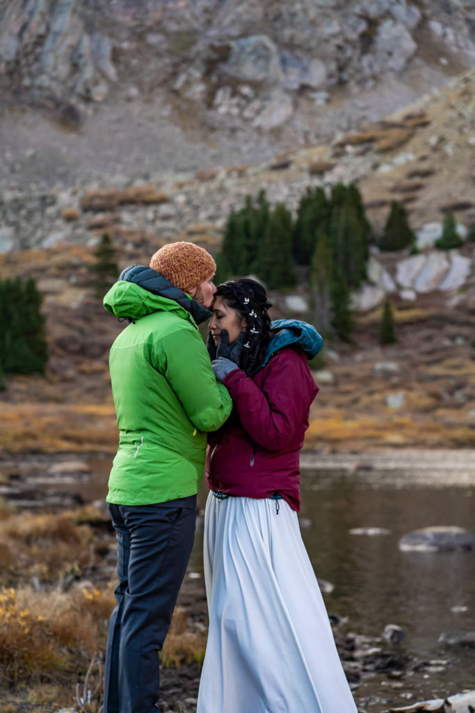 A bride and groom wearing puffy jackets over their wedding clothes, kissing in front of an alpine lake. Photo by Gabby Jockers Photography. Colorado elopement ideas, elopement inspiration, elopement ideas, Colorado elopement photographer, Colorado elopement photography, hiking elopement, backpacking elopement, Rocky Mountain national park wedding, rocky mountains, backpacking wedding, camping wedding, fall wedding, adventure wedding, adventurous elopement, mountain elopement, elopement with dog, dog of honor, best dog