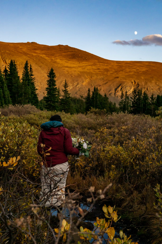 A married couple wearing wedding clothes and puffy jackets walk down a trail at sunset in the mountains. The bride has a silk bouquet. Photo by Gabby Jockers Photography. Colorado elopement ideas, elopement inspiration, elopement ideas, Colorado elopement photographer, Colorado elopement photography, hiking elopement, backpacking elopement, Rocky Mountain national park wedding, rocky mountains, backpacking wedding, camping wedding, fall wedding, adventure wedding, adventurous elopement, mountain elopement, elopement with dog, dog of honor, best dog
