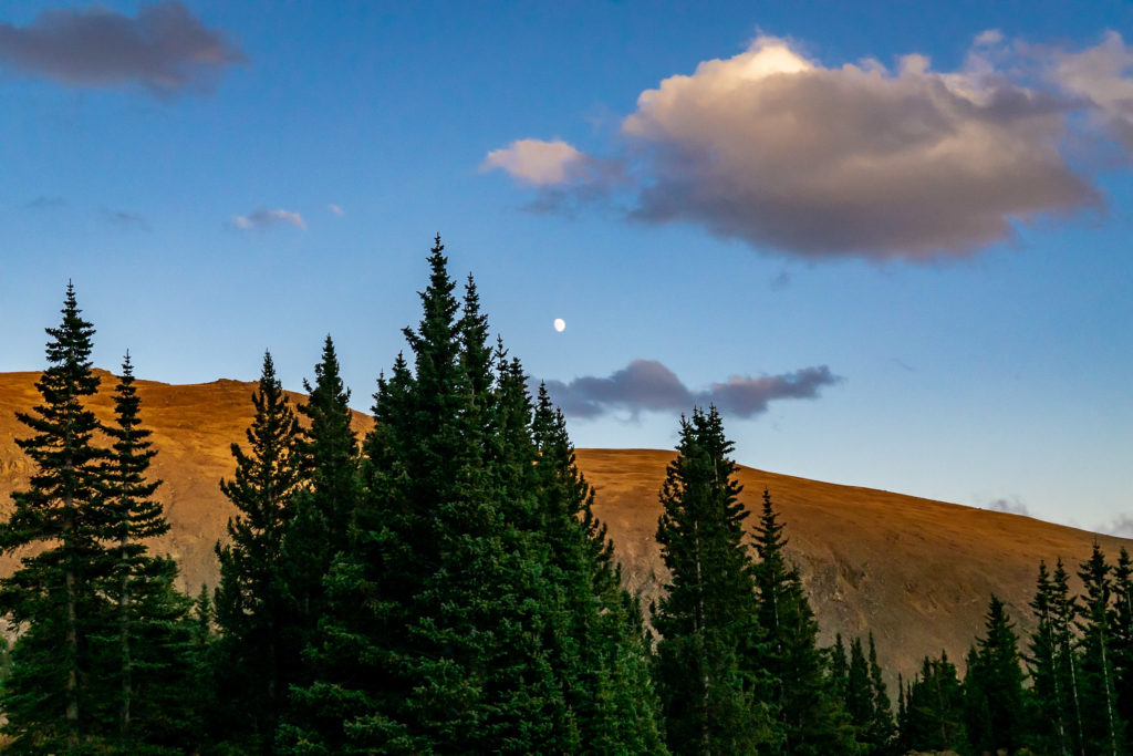 The moon rises over a mountain ridge at twilight. Photo by Gabby Jockers Photography. Colorado elopement ideas, elopement inspiration, elopement ideas, Colorado elopement photographer, Colorado elopement photography, hiking elopement, backpacking elopement, Rocky Mountain national park wedding, rocky mountains, backpacking wedding, camping wedding, fall wedding, adventure wedding, adventurous elopement, mountain elopement, elopement with dog, dog of honor, best dog