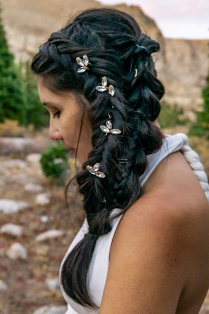 Bride with a braided wedding hairstyle and floral hair gems. Photo by Gabby Jockers Photography. Colorado elopement ideas, elopement inspiration, elopement ideas, Colorado elopement photographer, Colorado elopement photography, hiking elopement, backpacking elopement, Rocky Mountain national park wedding, rocky mountains, backpacking wedding, camping wedding, fall wedding, adventure wedding, adventurous elopement, mountain elopement, elopement with dog, dog of honor, best dog