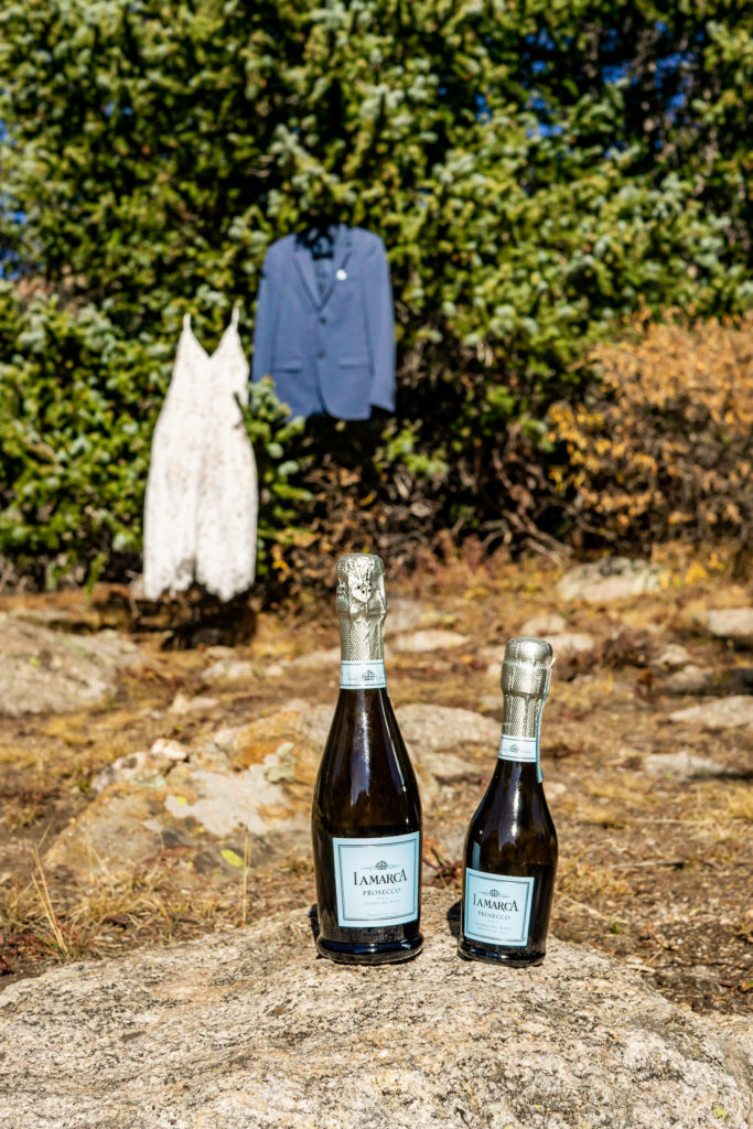 Two mini bottles of champagne in front of a lace wedding dress and blue sport coat on an outdoor elopement. Photo by Gabby Jockers Photography. Colorado elopement ideas, elopement inspiration, elopement ideas, Colorado elopement photographer, Colorado elopement photography, hiking elopement, backpacking elopement, Rocky Mountain national park wedding, rocky mountains, backpacking wedding, camping wedding, fall wedding, adventure wedding, adventurous elopement, mountain elopement, elopement with dog, dog of honor, best dog