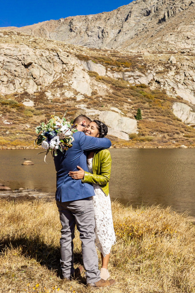A newly married couple hugs in front of an album lake. The bride wears a lace dress while holding a silk bouquet and green leather jacket and groom wears a blue sports coat. Photo by Gabby Jockers Photography. Colorado elopement ideas, elopement inspiration, elopement ideas, Colorado elopement photographer, Colorado elopement photography, hiking elopement, backpacking elopement, Rocky Mountain national park wedding, rocky mountains, backpacking wedding, camping wedding, fall wedding, adventure wedding, adventurous elopement, mountain elopement, elopement with dog, dog of honor, best dog