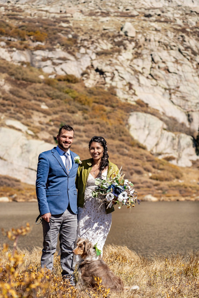 A newly married couple smiles in each others arms with their dog of honor. The bride wears a lace dress while holding a silk bouquet and green leather jacket and groom wears a blue sports coat. Photo by Gabby Jockers Photography. Colorado elopement ideas, elopement inspiration, elopement ideas, Colorado elopement photographer, Colorado elopement photography, hiking elopement, backpacking elopement, Rocky Mountain national park wedding, rocky mountains, backpacking wedding, camping wedding, fall wedding, adventure wedding, adventurous elopement, mountain elopement, elopement with dog, dog of honor, best dog
