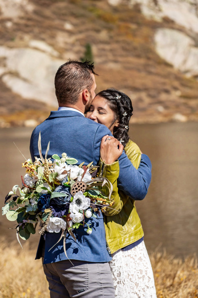 A newly married couple shares an intimate hug in front of an alpine lake. The bride wears a lace dress while holding a silk bouquet and green leather jacket and groom wears a blue sports coat. Photo by Gabby Jockers Photography. Colorado elopement ideas, elopement inspiration, elopement ideas, Colorado elopement photographer, Colorado elopement photography, hiking elopement, backpacking elopement, Rocky Mountain national park wedding, rocky mountains, backpacking wedding, camping wedding, fall wedding, adventure wedding, adventurous elopement, mountain elopement, elopement with dog, dog of honor, best dog