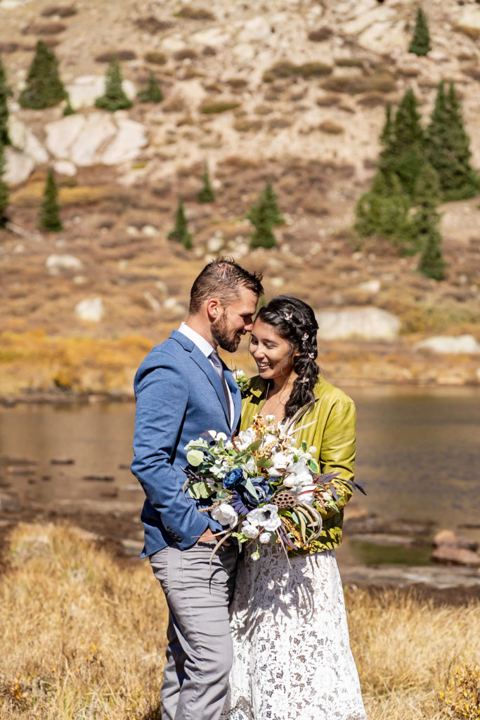 A couple stands together smiling in front of an alpine lake. The bride wears a lace dress while holding a silk bouquet and green leather jacket and groom wears a blue sports coat. Photo by Gabby Jockers Photography. Colorado elopement ideas, elopement inspiration, elopement ideas, Colorado elopement photographer, Colorado elopement photography, hiking elopement, backpacking elopement, Rocky Mountain national park wedding, rocky mountains, backpacking wedding, camping wedding, fall wedding, adventure wedding, adventurous elopement, mountain elopement, elopement with dog, dog of honor, best dog