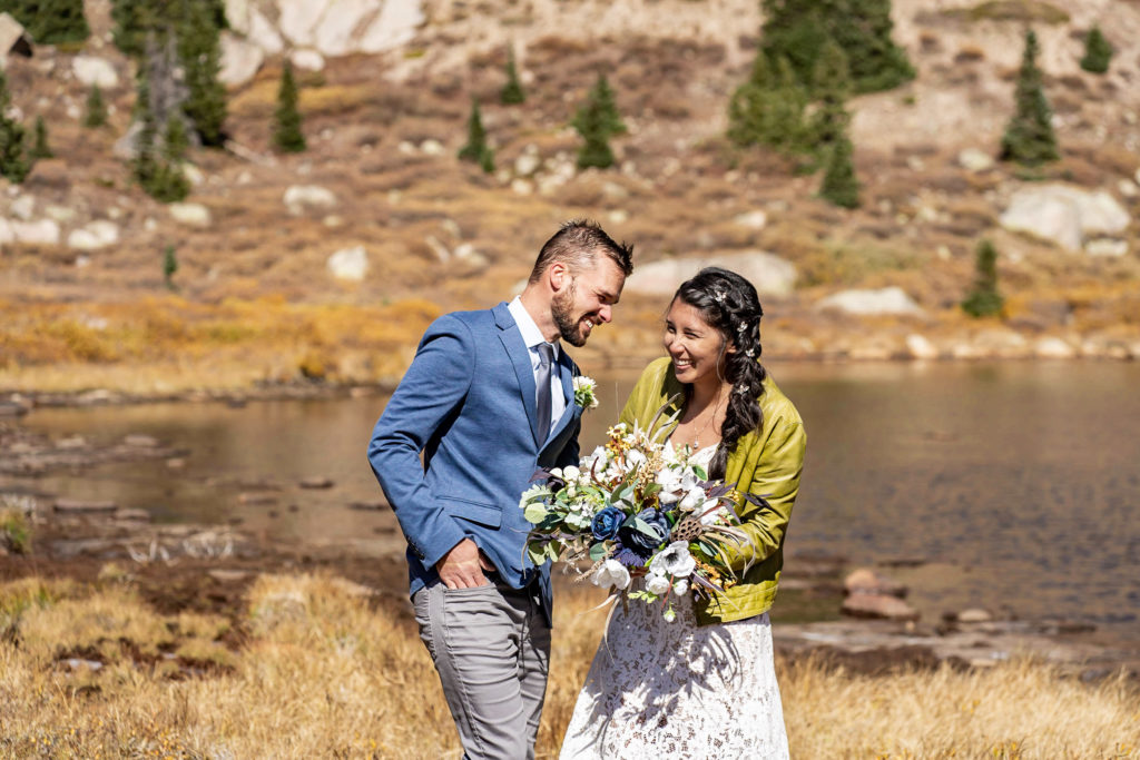 A couples laughs and has fun together by an alpine lake. The bride wears a lace dress while holding a silk bouquet and green leather jacket and groom wears a blue sports coat. Photo by Gabby Jockers Photography. Colorado elopement ideas, elopement inspiration, elopement ideas, Colorado elopement photographer, Colorado elopement photography, hiking elopement, backpacking elopement, Rocky Mountain national park wedding, rocky mountains, backpacking wedding, camping wedding, fall wedding, adventure wedding, adventurous elopement, mountain elopement, elopement with dog, dog of honor, best dog