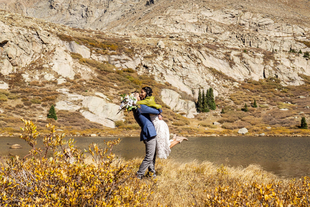 A groom picks up his bride and they kiss in front of an alpine lake. The bride wears a lace dress while holding a silk bouquet and green leather jacket and groom wears a blue sports coat. Photo by Gabby Jockers Photography. Colorado elopement ideas, elopement inspiration, elopement ideas, Colorado elopement photographer, Colorado elopement photography, hiking elopement, backpacking elopement, Rocky Mountain national park wedding, rocky mountains, backpacking wedding, camping wedding, fall wedding, adventure wedding, adventurous elopement, mountain elopement, elopement with dog, dog of honor, best dog