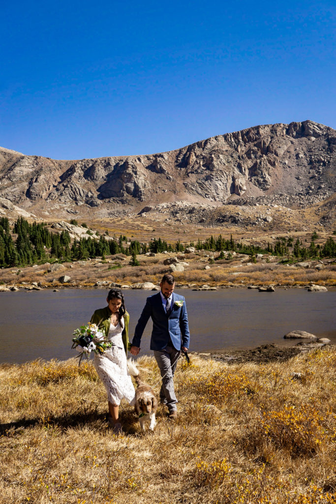 A couple walks hand in hand down the trail. The bride wears a lace dress while holding a silk bouquet and green leather jacket and groom wears a blue sports coat. Photo by Gabby Jockers Photography. Colorado elopement ideas, elopement inspiration, elopement ideas, Colorado elopement photographer, Colorado elopement photography, hiking elopement, backpacking elopement, Rocky Mountain national park wedding, rocky mountains, backpacking wedding, camping wedding, fall wedding, adventure wedding, adventurous elopement, mountain elopement, elopement with dog, dog of honor, best dog