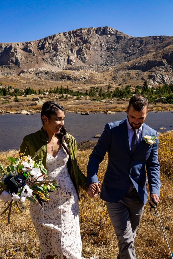 A couple walks hand in hand down the trail. The bride wears a lace dress while holding a silk bouquet and green leather jacket and groom wears a sports coat. Photo by Gabby Jockers Photography. Colorado elopement ideas, elopement inspiration, elopement ideas, Colorado elopement photographer, Colorado elopement photography, hiking elopement, backpacking elopement, Rocky Mountain national park wedding, rocky mountains, backpacking wedding, camping wedding, fall wedding, adventure wedding, adventurous elopement, mountain elopement, elopement with dog, dog of honor, best dog