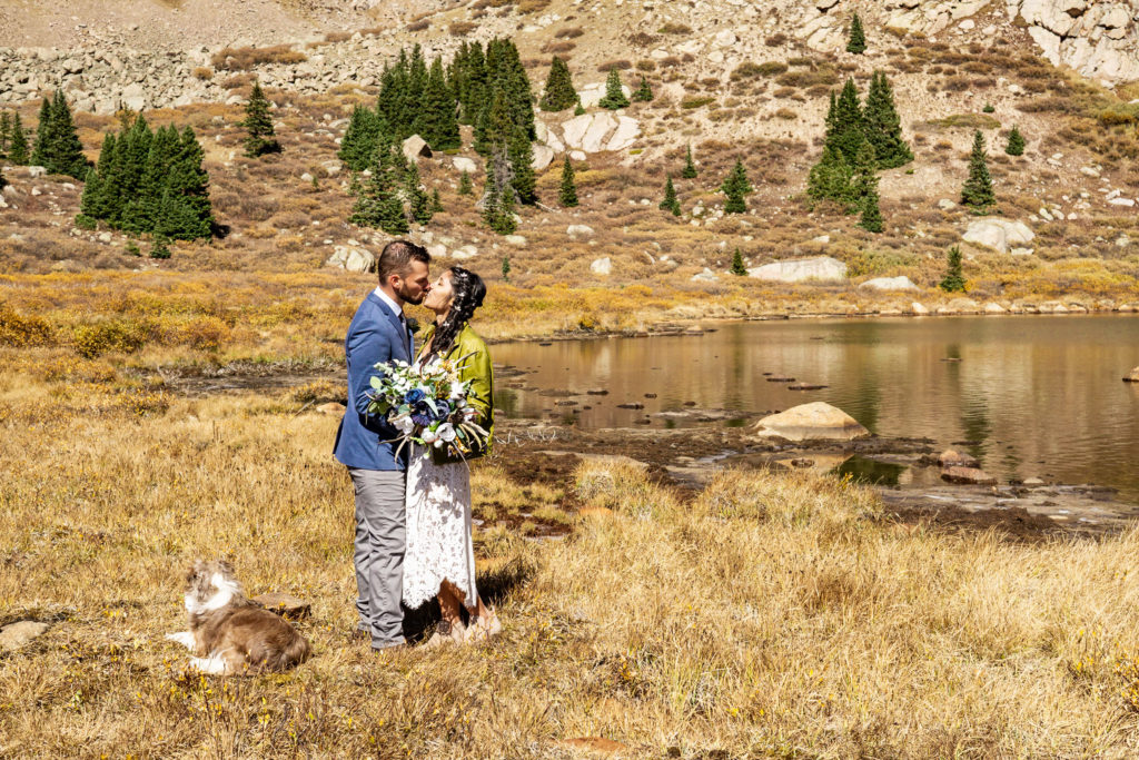 A couple kisses in front of an album lake. The bride wears a lace dress while holding a silk bouquet and green leather jacket and groom wears a sports coat. Photo by Gabby Jockers Photography. Colorado elopement ideas, elopement inspiration, elopement ideas, Colorado elopement photographer, Colorado elopement photography, hiking elopement, backpacking elopement, Rocky Mountain national park wedding, rocky mountains, backpacking wedding, camping wedding, fall wedding, adventure wedding, adventurous elopement, mountain elopement, elopement with dog, dog of honor, best dog