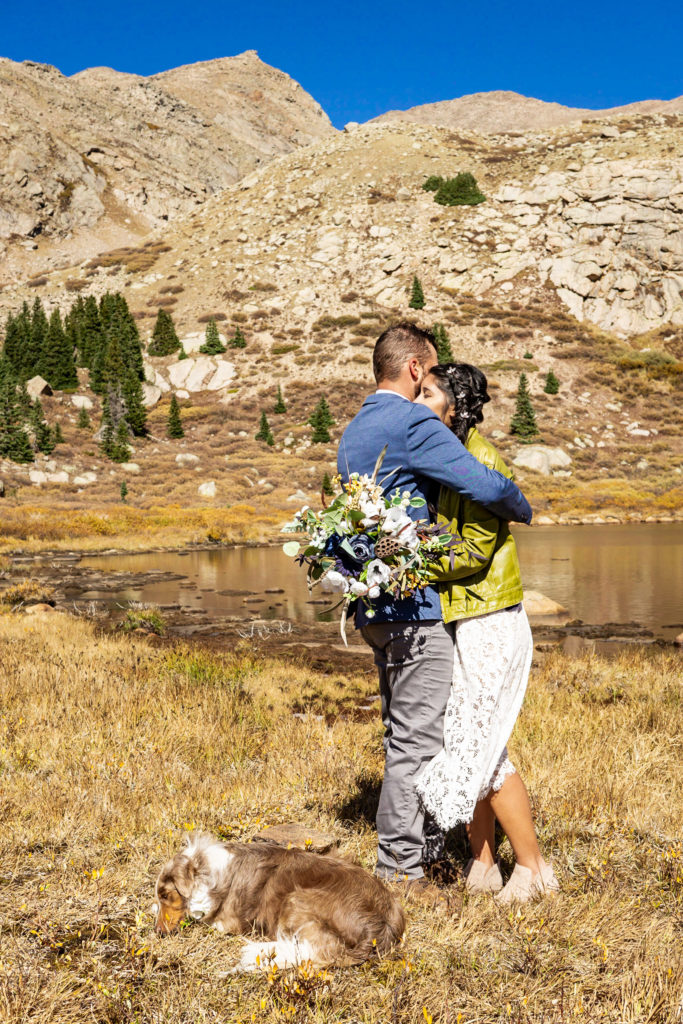 A couple embracing in front of an alpine lake. The bride wears a lace dress while holding a silk bouquet and green leather jacket and groom wears a sports coat. Photo by Gabby Jockers Photography. Colorado elopement ideas, elopement inspiration, elopement ideas, Colorado elopement photographer, Colorado elopement photography, hiking elopement, backpacking elopement, Rocky Mountain national park wedding, rocky mountains, backpacking wedding, camping wedding, fall wedding, adventure wedding, adventurous elopement, mountain elopement, elopement with dog, dog of honor, best dog