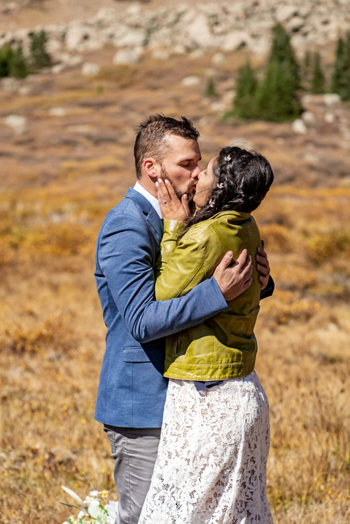 A newly married couple sharing a passionate first kiss - the bride wears a lace dress and green leather jacket and groom wears a sports coat. Photo by Gabby Jockers Photography. Colorado elopement ideas, elopement inspiration, elopement ideas, Colorado elopement photographer, Colorado elopement photography, hiking elopement, backpacking elopement, Rocky Mountain national park wedding, rocky mountains, backpacking wedding, camping wedding, fall wedding, adventure wedding, adventurous elopement, mountain elopement, elopement with dog, dog of honor, best dog
