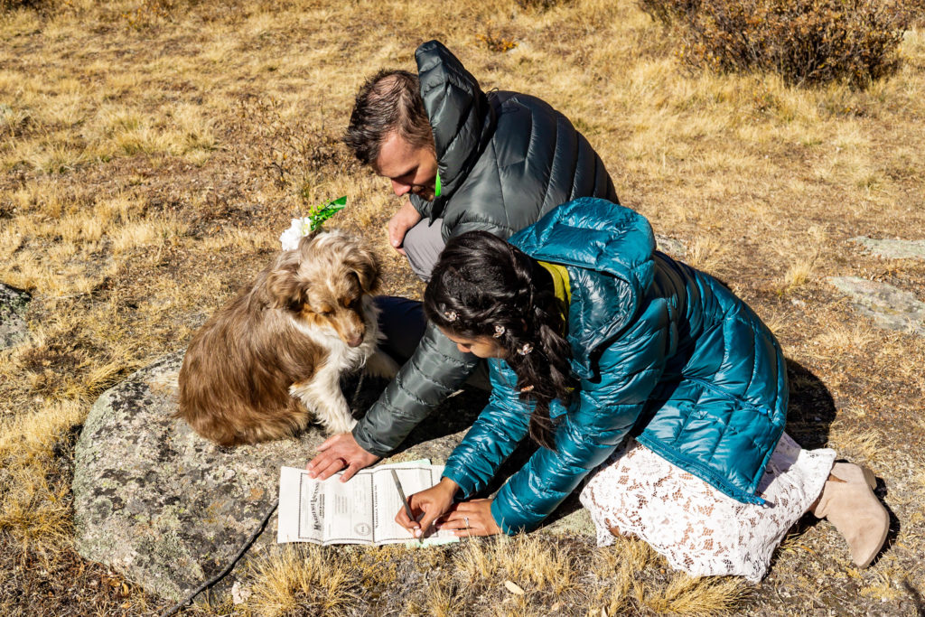 A couple wearing wedding clothes and puffy jackets sign their marriage certificate while sitting on the ground by an alpine lake. Self Solemnize in Colorado. Photo by Gabby Jockers Photography. Colorado elopement ideas, elopement inspiration, elopement ideas, Colorado elopement photographer, Colorado elopement photography, hiking elopement, backpacking elopement, Rocky Mountain national park wedding, rocky mountains, backpacking wedding, camping wedding, fall wedding, adventure wedding, adventurous elopement, mountain elopement, elopement with dog, dog of honor, best dog