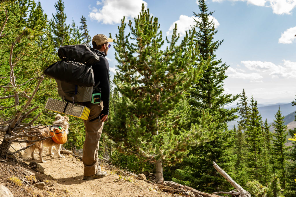 A man with backpacking gear and suit strapped on, he's looking at the mountain view with his dog. Photo by Gabby Jockers Photography. Colorado elopement ideas, elopement inspiration, elopement ideas, Colorado elopement photographer, Colorado elopement photography, hiking elopement, backpacking elopement, Rocky Mountain national park wedding, rocky mountains, backpacking wedding, camping wedding, fall wedding, adventure wedding, adventurous elopement, mountain elopement, elopement with dog, dog of honor, best dog