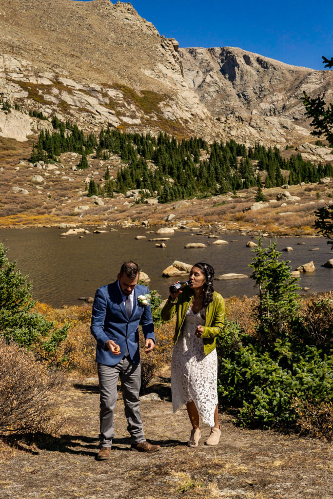 A newly married couple doing a champagne toast in front of a colorado alpine lake. Photo by Gabby Jockers Photography. Colorado elopement ideas, elopement inspiration, elopement ideas, Colorado elopement photographer, Colorado elopement photography, hiking elopement, backpacking elopement, Rocky Mountain national park wedding, rocky mountains, backpacking wedding, camping wedding, fall wedding, adventure wedding, adventurous elopement, mountain elopement, elopement with dog, dog of honor, best dog